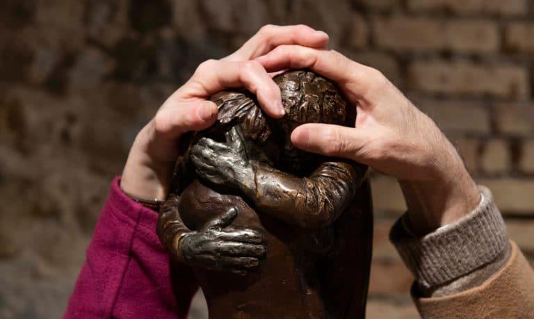 Due mani esplorano una scultura di bronzo raffigurante due mani intrecciate