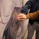 mani che esplorano un'opera d'arte in rilievo
